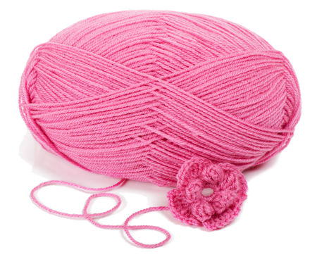 skein: pink ball of yarn crocheted flower  isolated on white