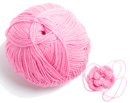 acrylic yarn: Pink yarn ball for knitting and   flower of crochet pattern isolated on white