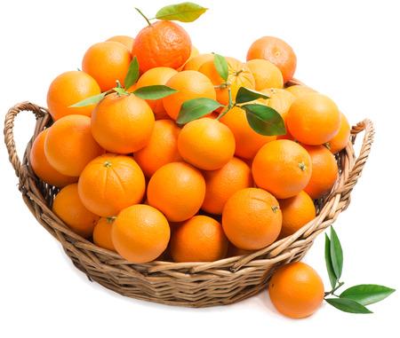 Sinaasappelen met bladeren in een grote mand op wit wordt geïsoleerd