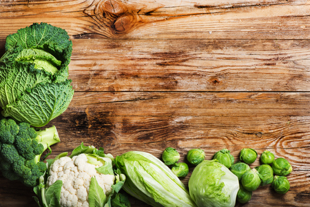 Fresh green  vegetables  on a rustic wooden table. photo