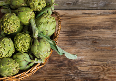 closeup of artichokes in a basket on a rustic wooden table  Stock Photo