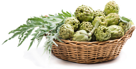 Globe artichokes with leaves  in a wicker basket over white Stock Photo