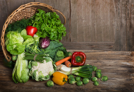 Composition with vegetables  in wicker basket on the wooden table