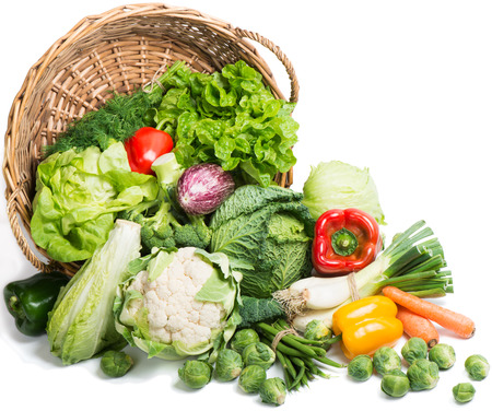 Fresh picked  vegetables in a basket  is scattered on a  white background