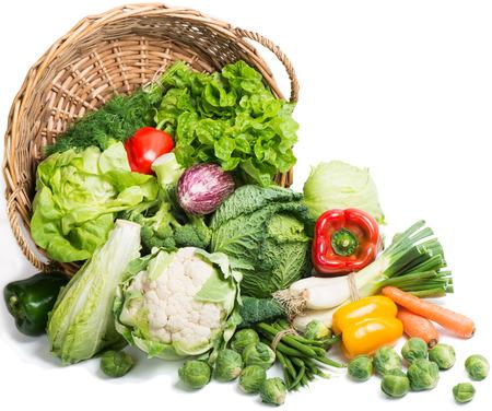 Vers geplukte groenten in een mand wordt verspreid op een witte achtergrond