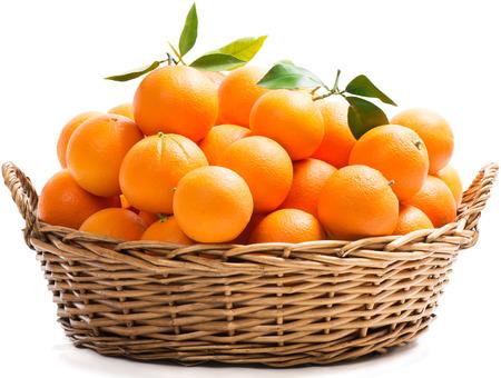 Een rieten mand vol verse oranje vruchten, geïsoleerd op een witte achtergrond.