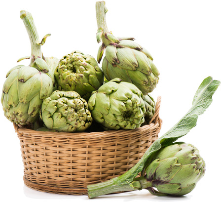 Fresh  artichokes in a basket with one on the surface in the foreground.  Stock Photo