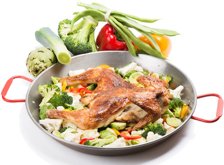 Fried chicken with vegetables in the pan and fresh vegetables on background  photo