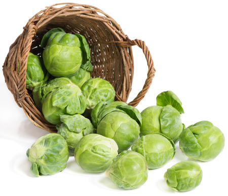 underlying: underlying basket with brussel sprouts  spilling on a white