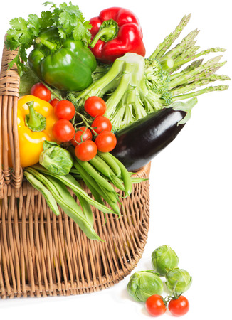 Half of wicker basket different vegetables in basket isolated on white photo