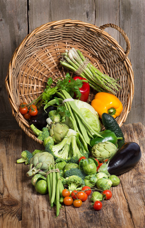underlying basket with of mix vegetables  spilling on rustic wooden background  photo