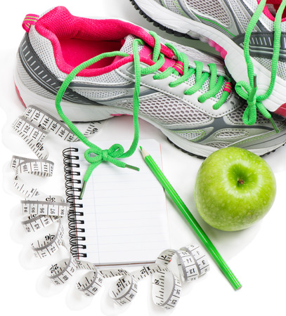 journals:  Sports shoes, notebook, pencil and fresh apple isolated on white. Planning of a diet. Stock Photo