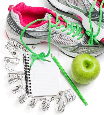 Sportschoenen, notebook, potlood en verse appel geïsoleerd op wit. Planning van een dieet.