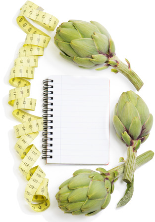 Raw artichokes, notepad with measure tape over white background
