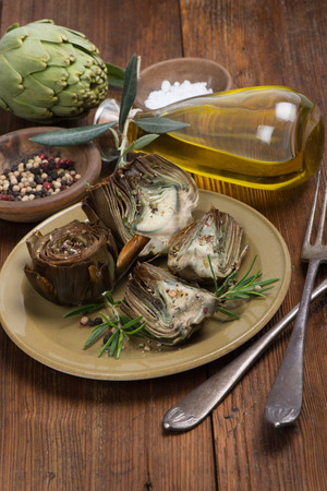 A plate with cooked artichokes,  served with olive oil,  pepper and salt on the  wooden table  photo