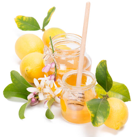 Honey, fresh lemons with  leaves and white flowers of lemon, isolated on white background   photo