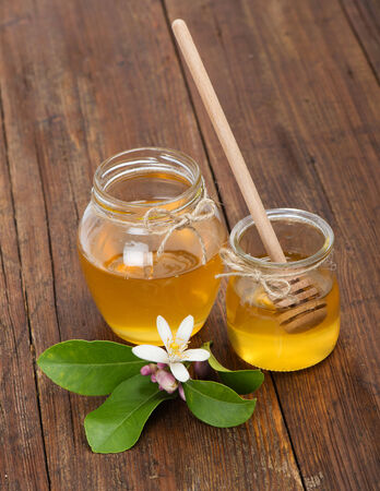 Honey jars with honey dipper and blossom of lemon on wood table  photo