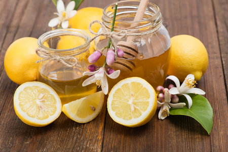 Jars of honey and  lemons with flowers  on wooden table  photo