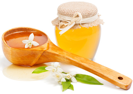 blossom honey:  Honey of flowers of an orange tree, blossom,  honey pouring from the  ladle, isolated on white background.