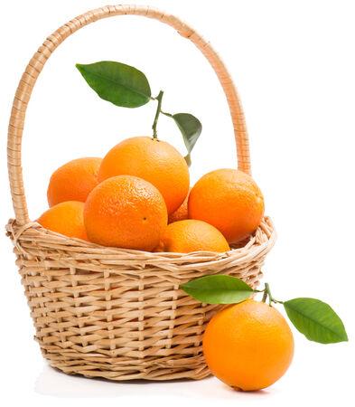 Orangen mit Blättern im Weidenkorb mit einem auf der Oberfläche im Vordergrund, isoliert auf weißem Hintergrund.