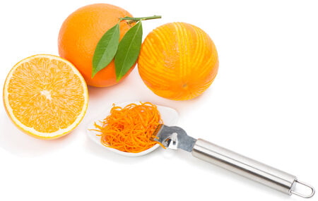 Halved and whole orange fruits,  zest in a white bowl, zester.  Isolated on white background. photo