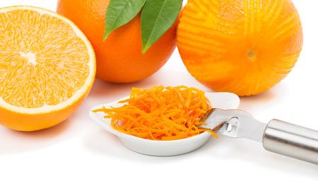 Orange zest in a white bowl , orange fruits with leaves , zeste.  Isolated on white background.  photo