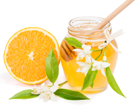 drizzler:  Half orange fruit, blossom and opened honey jar with drizzler inside, isolated on white  Stock Photo