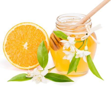 blossom honey:  Half orange fruit, blossom and opened honey jar with drizzler inside, isolated on white  Stock Photo
