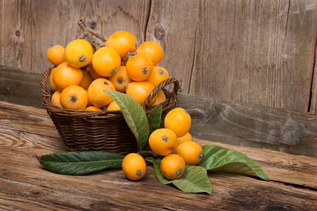 loquats on a wicker basket  on wooden background Stockfoto