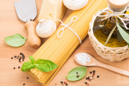 Composition of pasta, olive oil, champignons and cheese over wooden  background photo