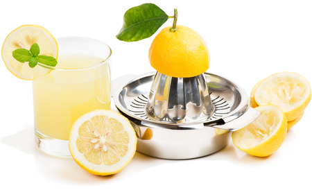 juice squeezer: Glass of lemon juice, squeezer and half squeezed lemons  on white background