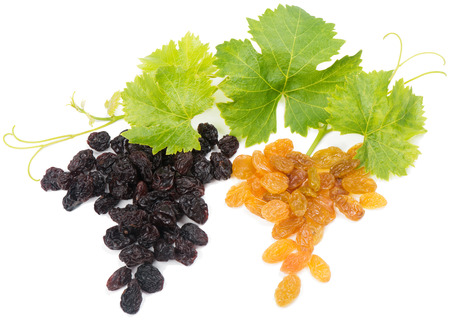 raisins:  Black and yellow raisins with leaves in form of a grape bunch, on a white