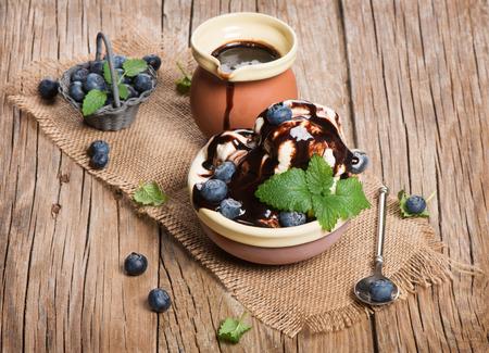 coppa di gelato: Gelato dessert con mirtilli succosi sul tavolo in legno
