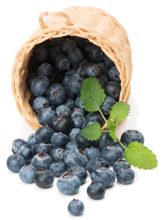 Blueberries scattered from  wicker basket on white background photo