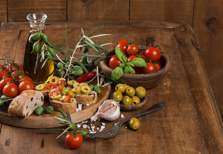 Italian tomato bruschetta with chopped olives, garlic, herbs and olive oil on  ciabatta bread on the wooden table photo