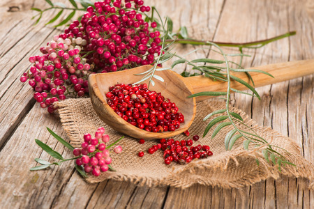 peppertree: fresh and dried pink pepper on a wooden table