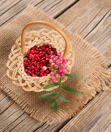 peppertree: red peppercorns on a twig and dry in a basket on a wooden table
