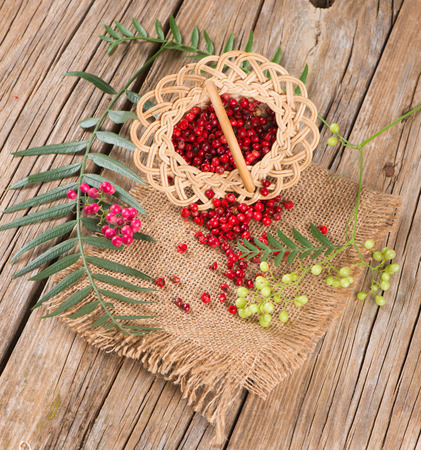peppertree: pink peppercorns scattered from wicker basket on wooden background