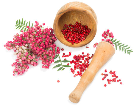 peppertree:  Pink peppercorns is scattered on a white background from wooden mortar and twigs of peruvian pepper tree isolated on white background