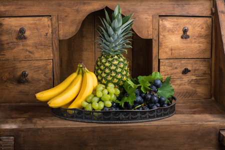 pantry: Fresh fruits (pineapple, banana, grapes) on a tray on wooden background