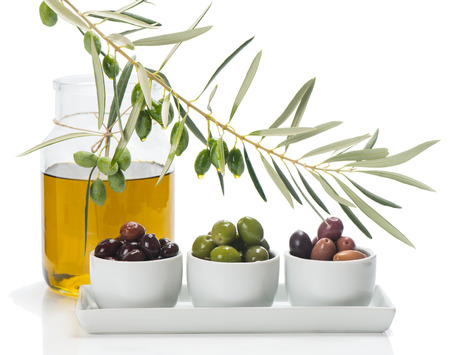 different varieties of olives marinated in white bowls and twig  of olive tree, jar of olive oil isolated on white