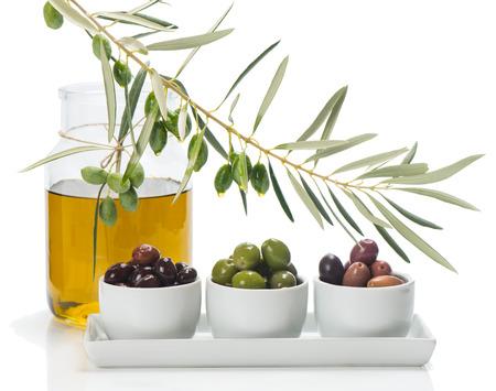 verschillende soorten olijven gemarineerd in witte kommen en takje van de olijfboom, kruikje olijfolie geïsoleerd op wit Stockfoto
