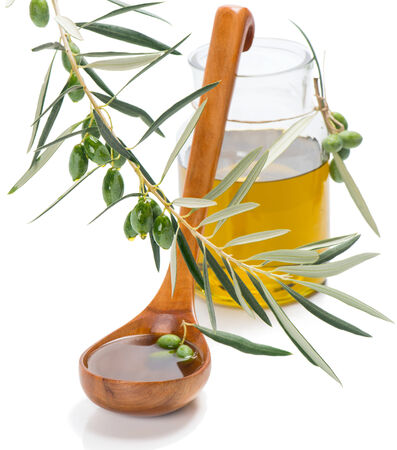 ladle: olive oil drops falling from olives in a ladle and jar with oil isolated on white