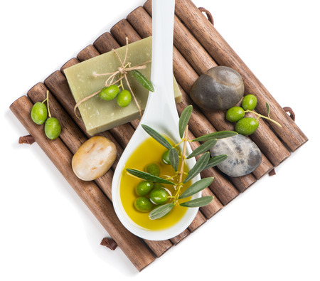 Olive oil with olive soap and spa stones isolated on white, top view