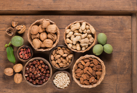 Assorted nuts (walnut,  almond, peanut, pine nuts, hazelnut) in a wooden bowls and baskets Stok Fotoğraf
