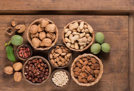Assortiment noten (walnoten, amandelen, pinda's, pijnboompitten, hazelnoot) in een houten kommen en manden