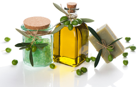 Natural spa setting with olives and olive oil products: bath salt, natural soap and olive oil isolated on white background.