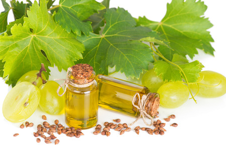Green grape with seeds and oil bottles isolated on white background.