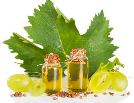 Grape seed oil in a glass bottles and grapes with leaves on white photo