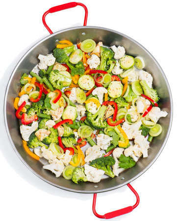 stirring:  assorted cut ripe vegetables  in a frying pan from top on white background  Stock Photo